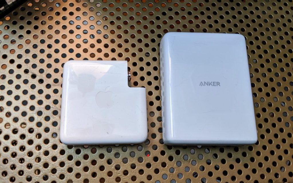 MacBook Pro power brick (left) next to White Anker Atom PD 4 Charging station (right)